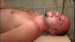 Muscled bald gay stud gets blowjob in the gym